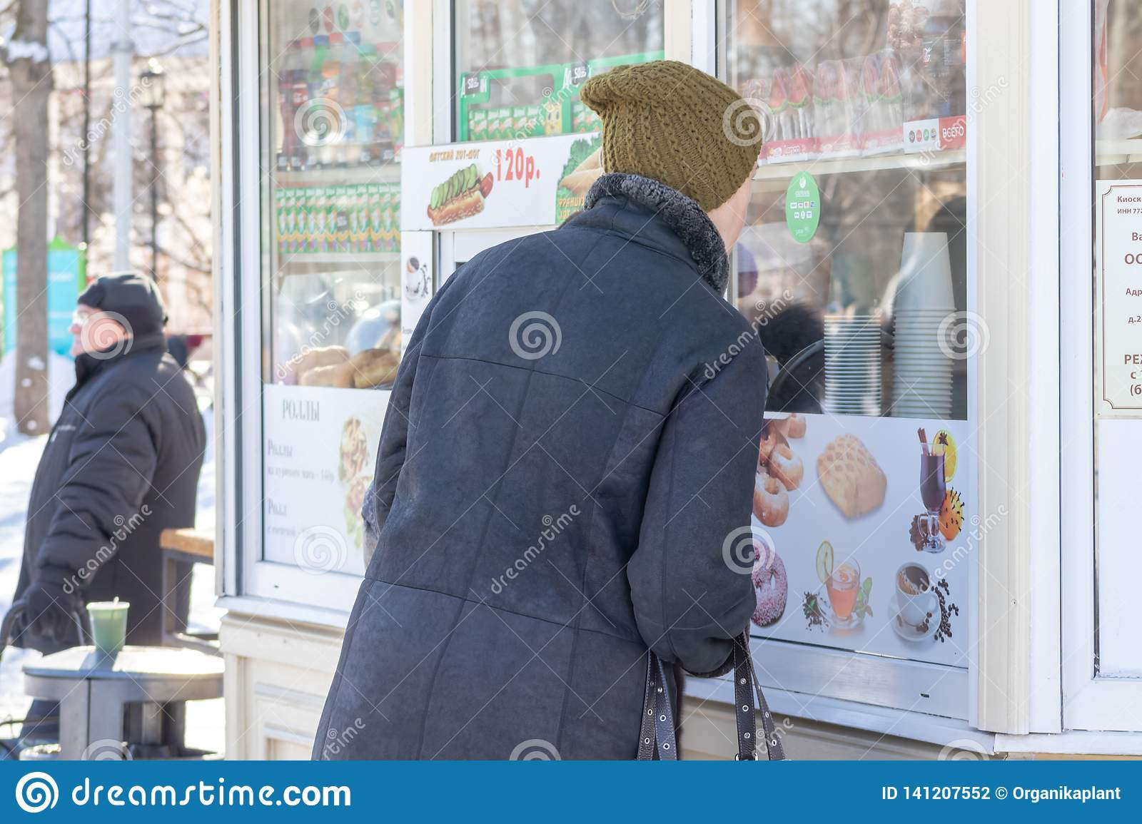 MOSCOW, RUSSIA - MARCH 02, 2019: A man buying street fast food and hot drinks in the stall during the stroll in a city park in