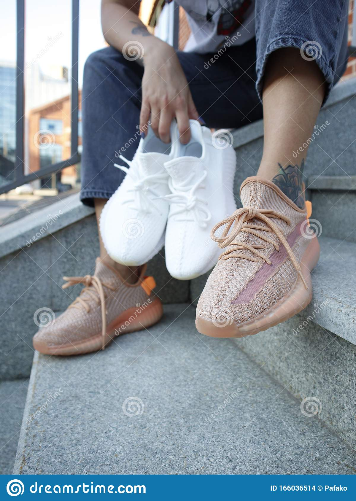 A Girl In Jeans And Cream Adidas Yeezy