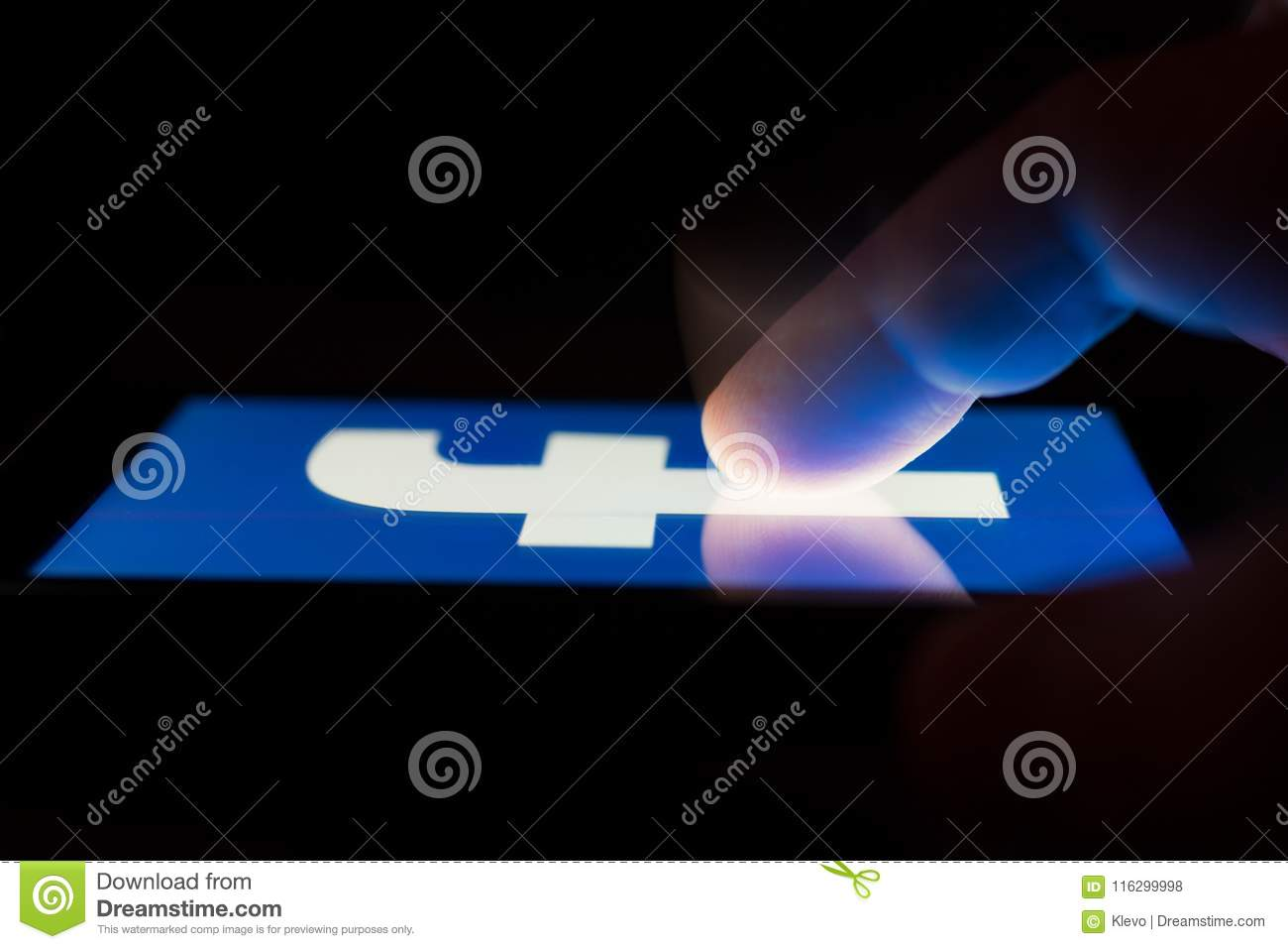 MOSCOW, RUSSIA - May 9, 2018: A smartphone lying on a table in the dark, displaying the logo of the Facebook.