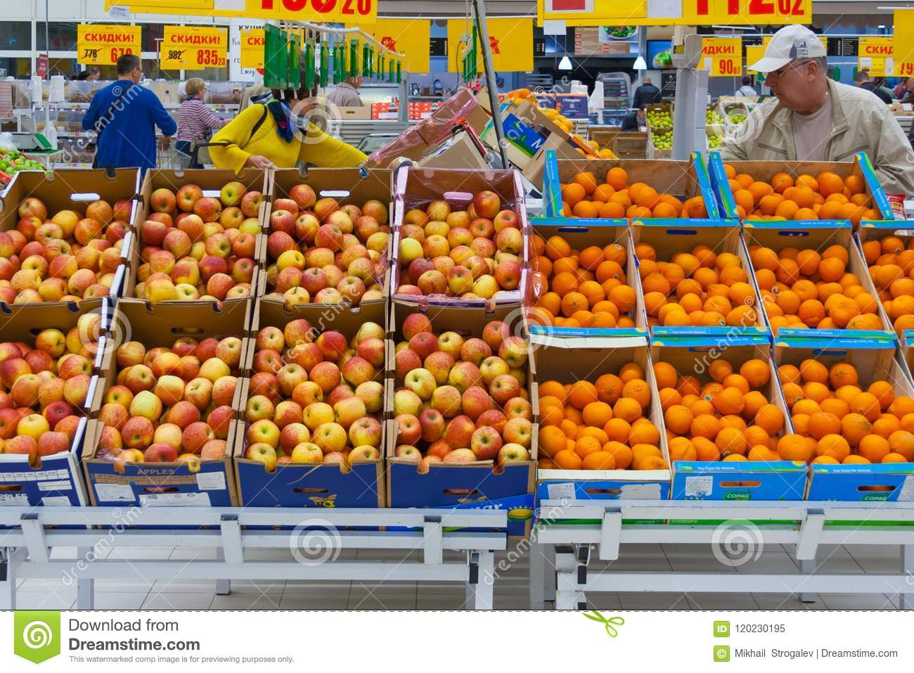 View of a rows of cartons boxes with apples and oranges in supermarket editorial