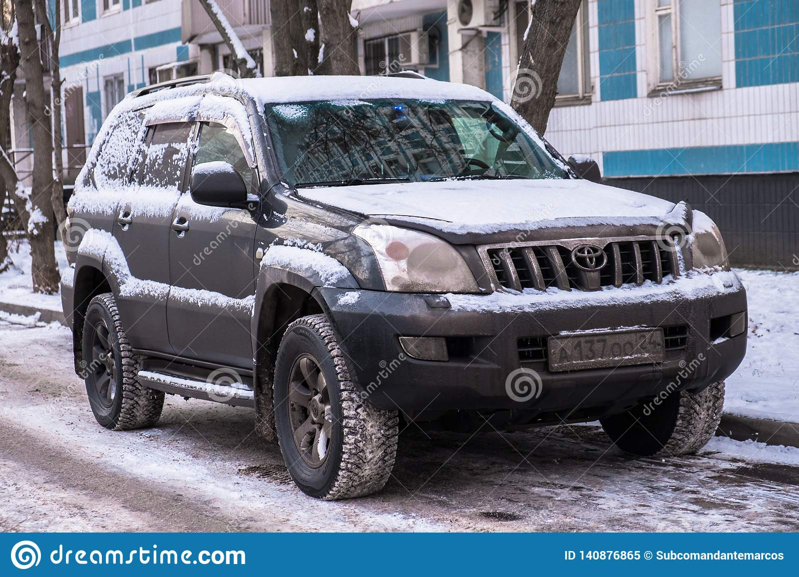 MOSCOW, RUSSIA,NOVEMBER,28.2018:Abandoned snow covered car Toyota Land Cruiser on a big city street.Consequences of snowfall