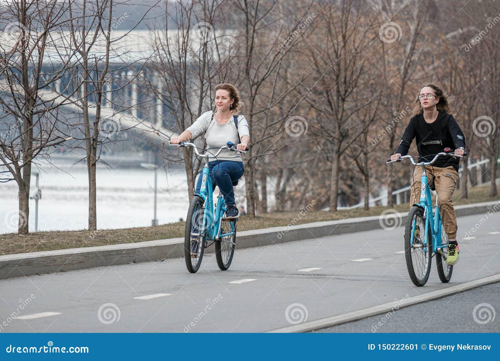 Moscow Ryssland E Två unga flickor rider runt om staden på blåa cyklar Sund livsstil sportfritid