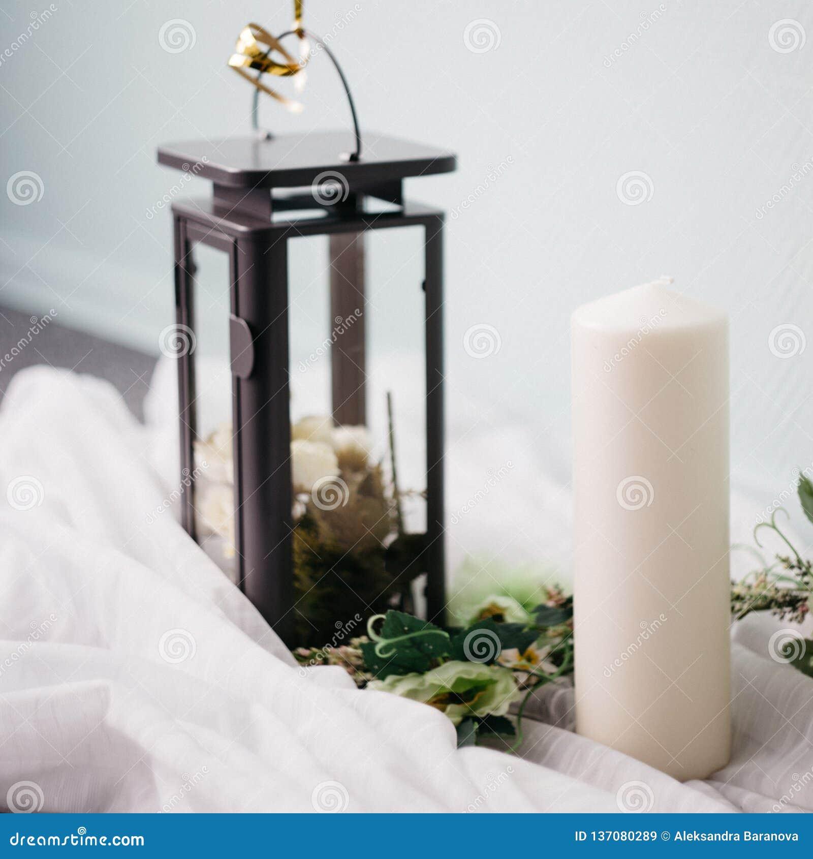 Moskau, Russland - 06 10 2018: schwarze Metalllampe mit weißen Rosen, Kerze und Blumen auf hellem Hintergrund, Hauptdekor