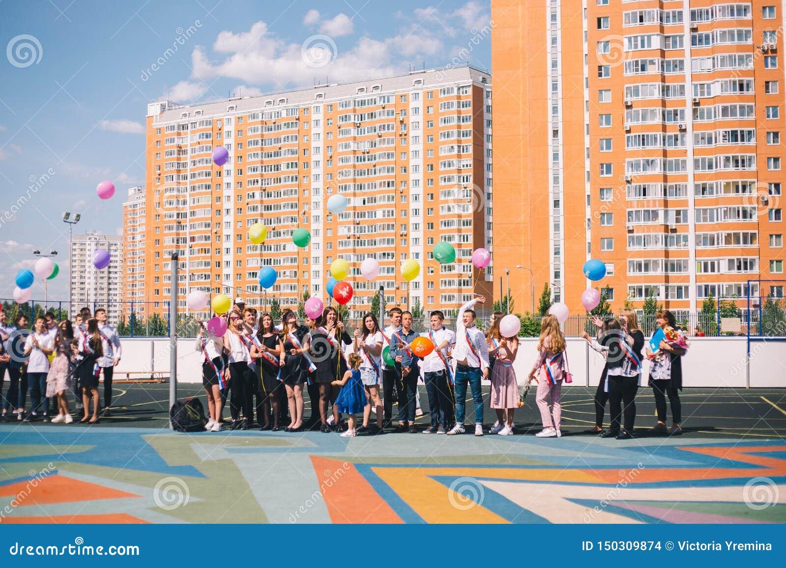 Moskou, Rusland - 22 Mei 2019: De gediplomeerden van de school zijn in de yard en laten de ballons