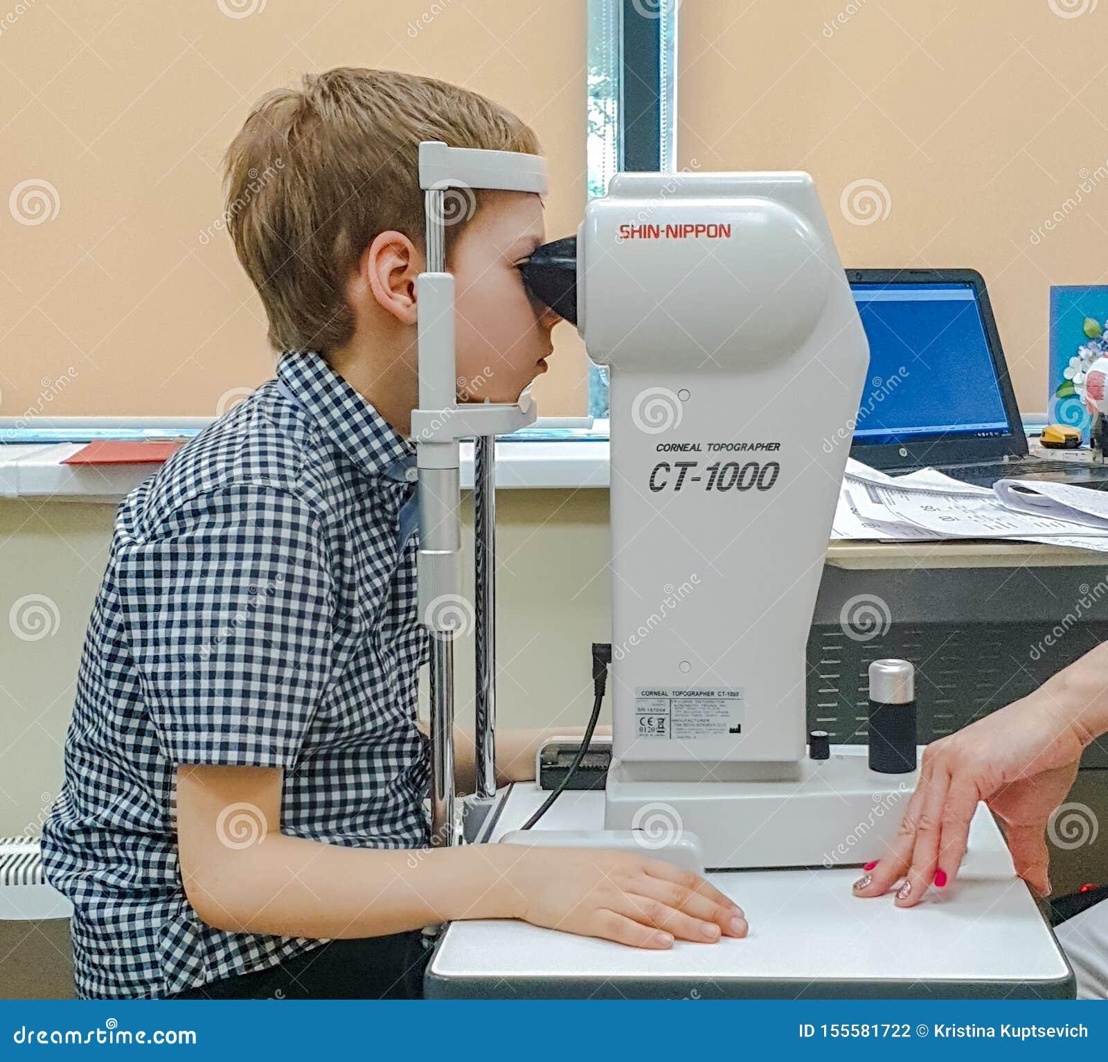 Moskou, Rusland - Mei 20, 2019: Een jongen bij een benoeming met een oftalmoloog controleert visie op het apparaat Kindgezondheid