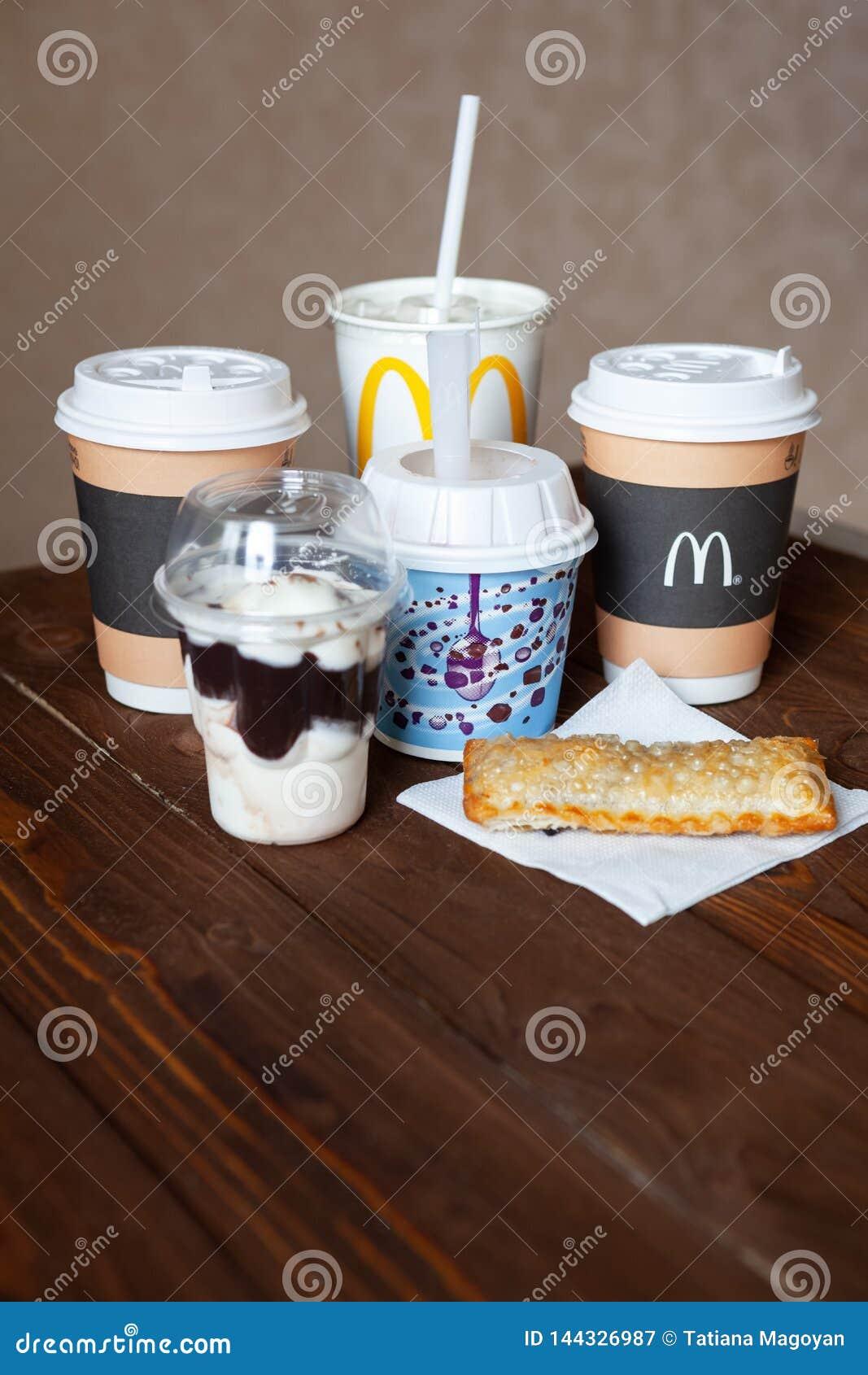 Moskva Ryssland - April 06, 2019: Mcdonald matleverans Efterrätter och varma drinkar på trätabellen Närbild Slapp fokus vertikalt