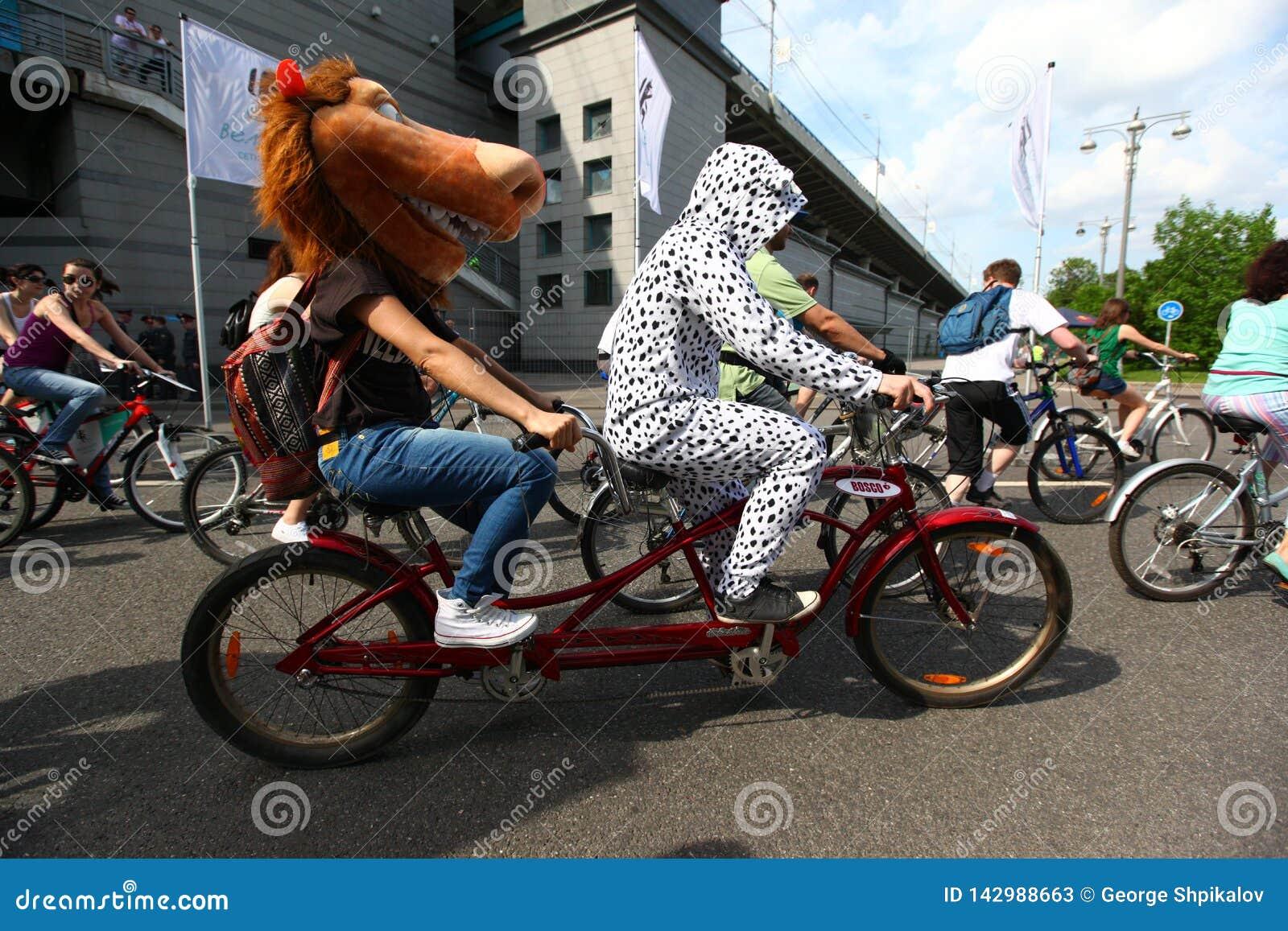 MOSKVA RYSSLAND - 20 Maj 2002: Att cykla för stad ståtar, hästen, och dalmationen kostymerade deltagare på en tandem cykel