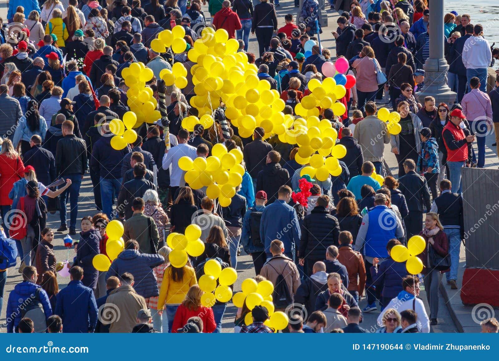 Moskva Ryssland - Maj 01, 2019: Folk med gula ballonger på den Kremlevskaya invallningen Demonstration f?r Maj dag i Moskva