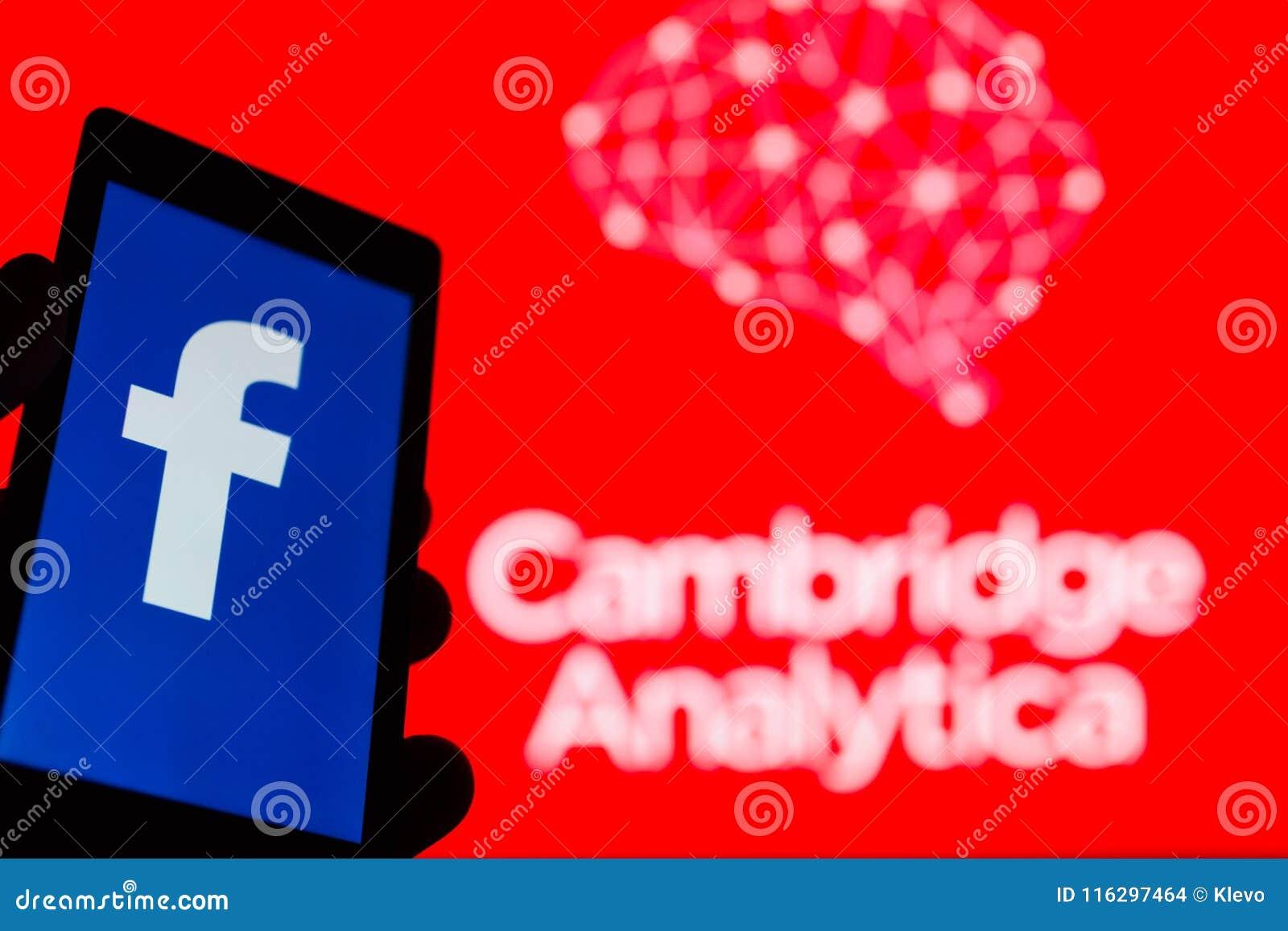 MOSKVA RYSSLAND - MAJ 9, 2018: Smartphone i hand med logo av det populära sociala nätverket Facebook Cambridge Analytica emblem