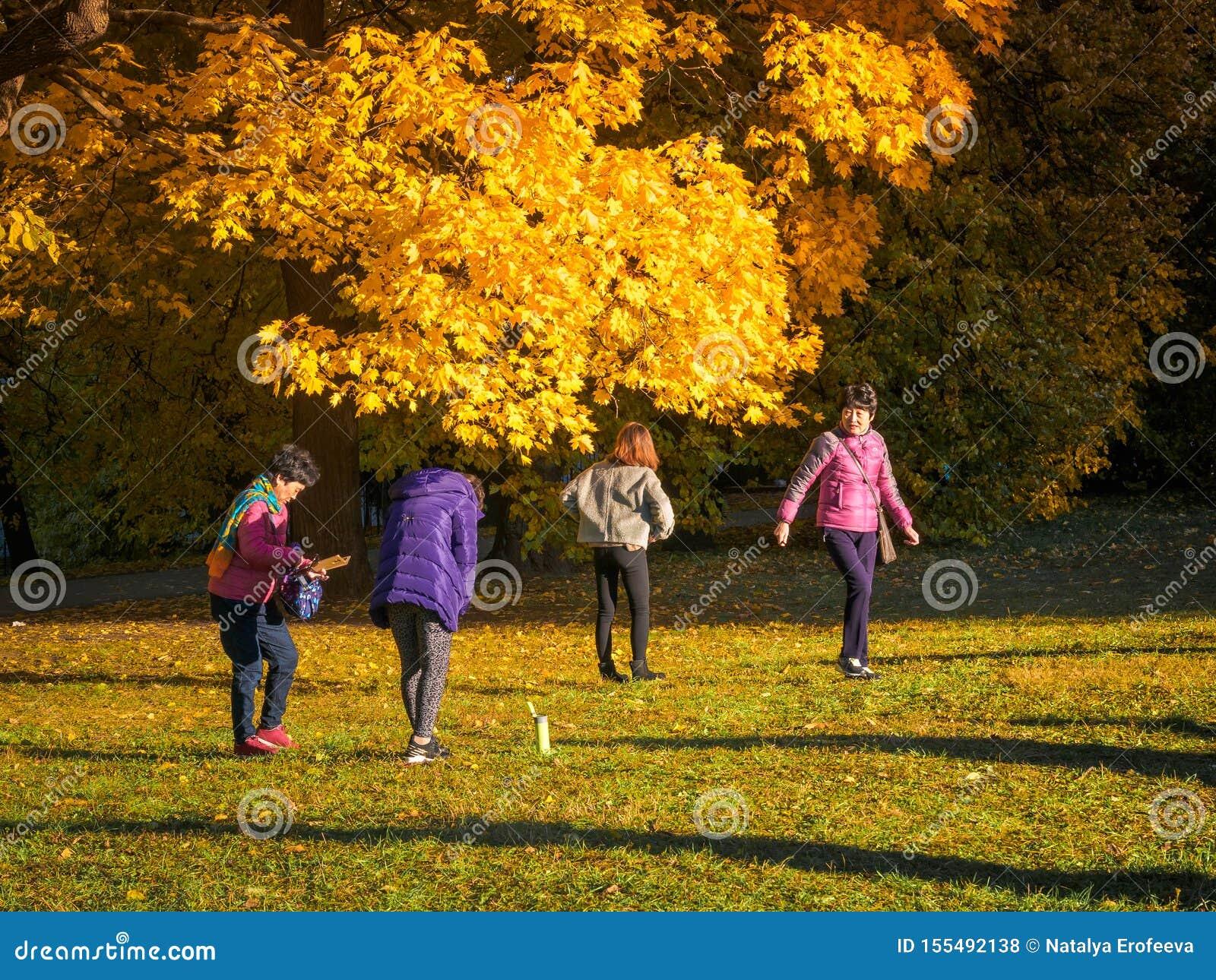 Moskwa Rosja, Październik, - 11, 2018: Chiński turystów spacerów jesieni park Azjatyccy ludzie biorą obrazki na tle a