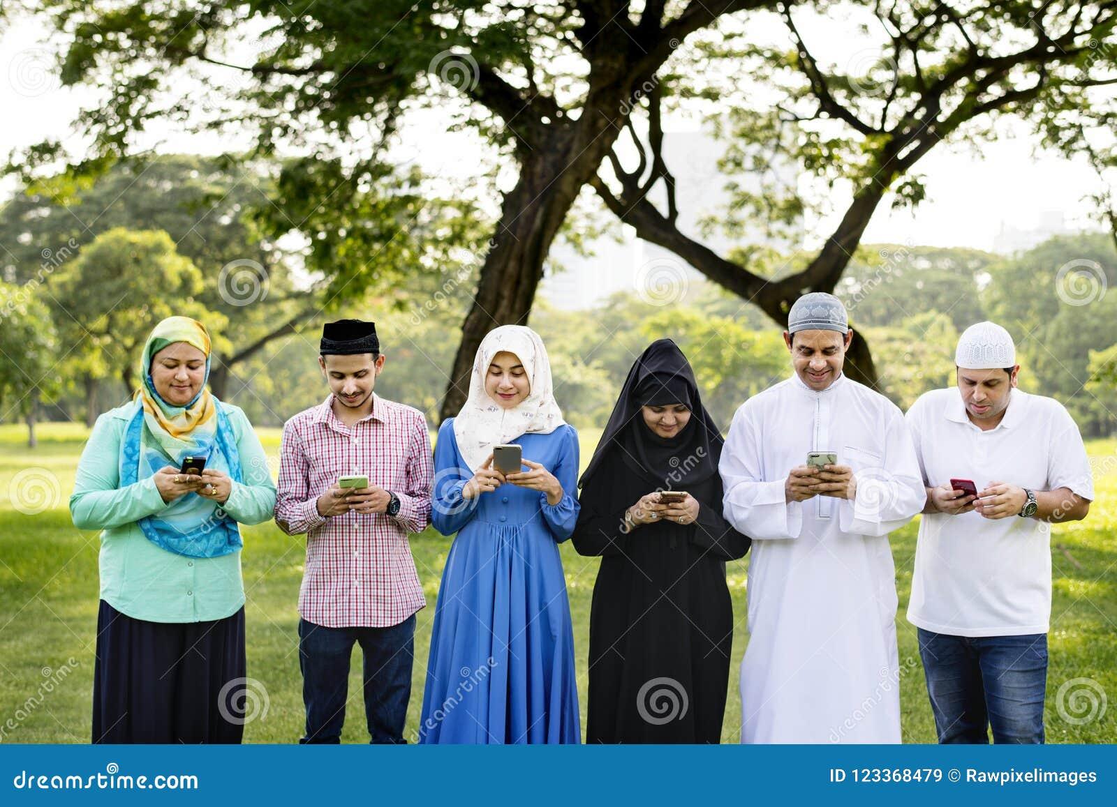 Moslemische Familie unter Verwendung der Smartphones im Park