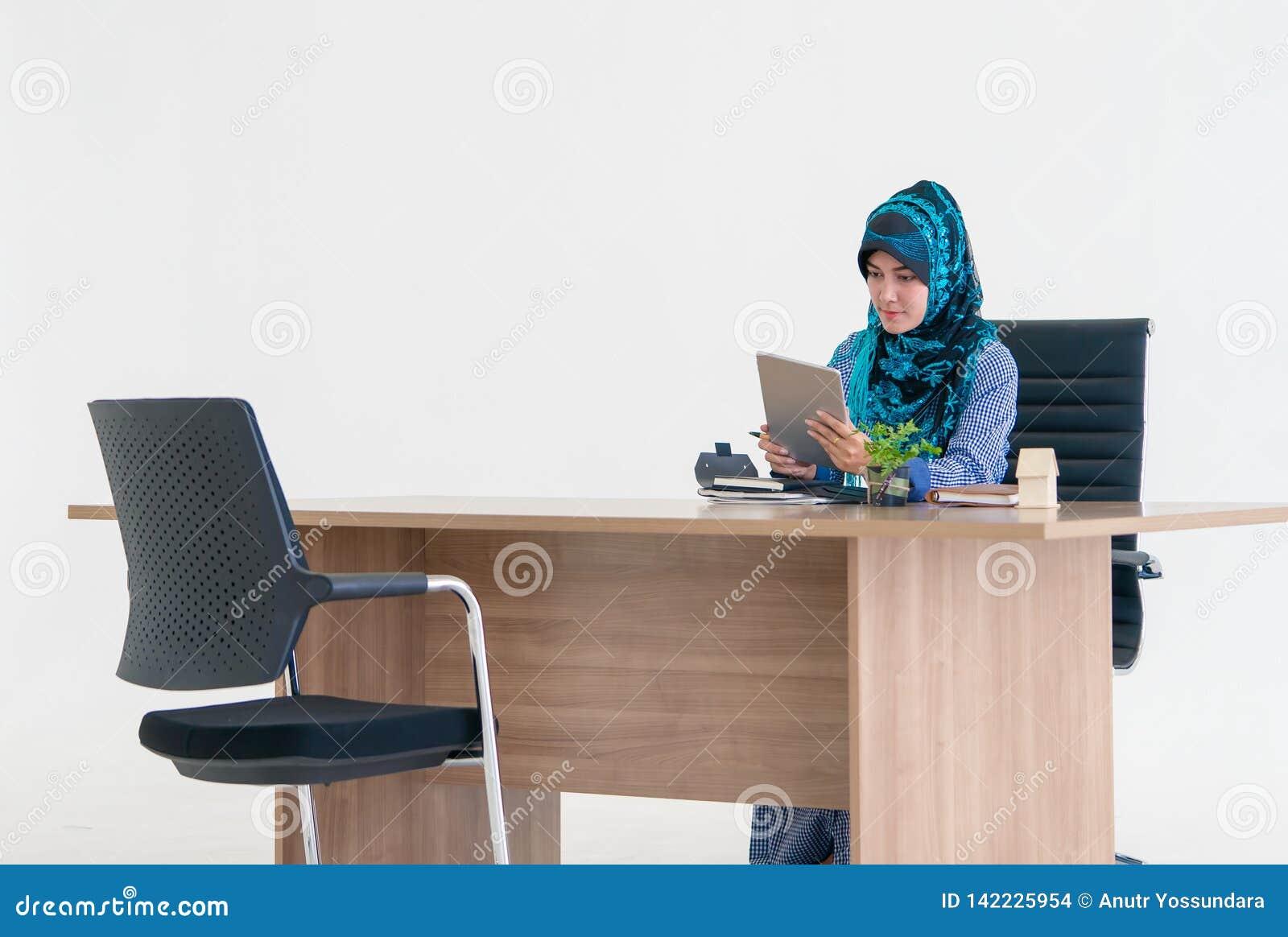 Moslemische Frau, die digitale Tablette auf Bürotisch verwendet