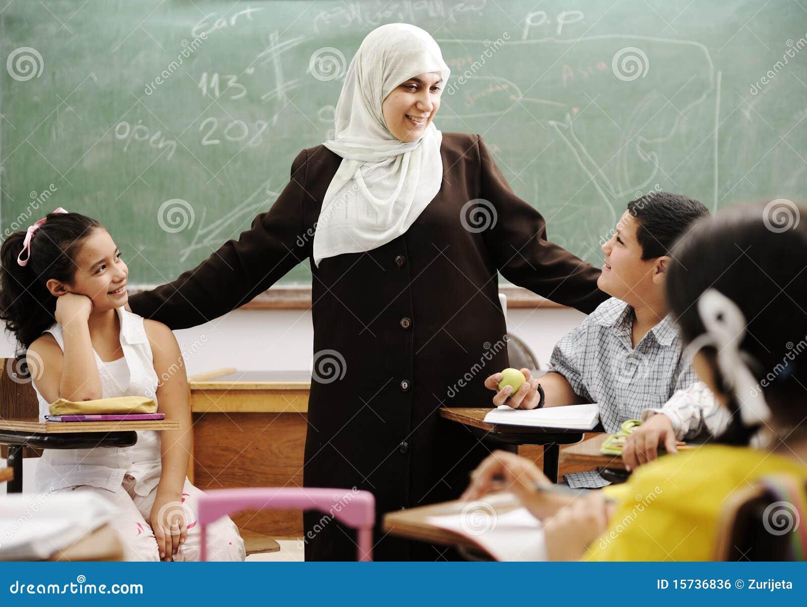 Moslemischer weiblicher Lehrer mit Kindern im Klassenzimmer