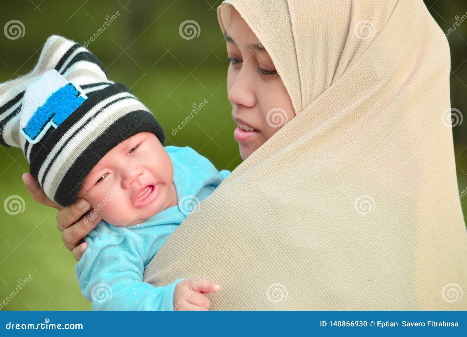 Moslimhijabimoeder die zijn schreeuwende zuigelingsbaby in haar wapen kalmeert bij openluchtpark in zonnige dag