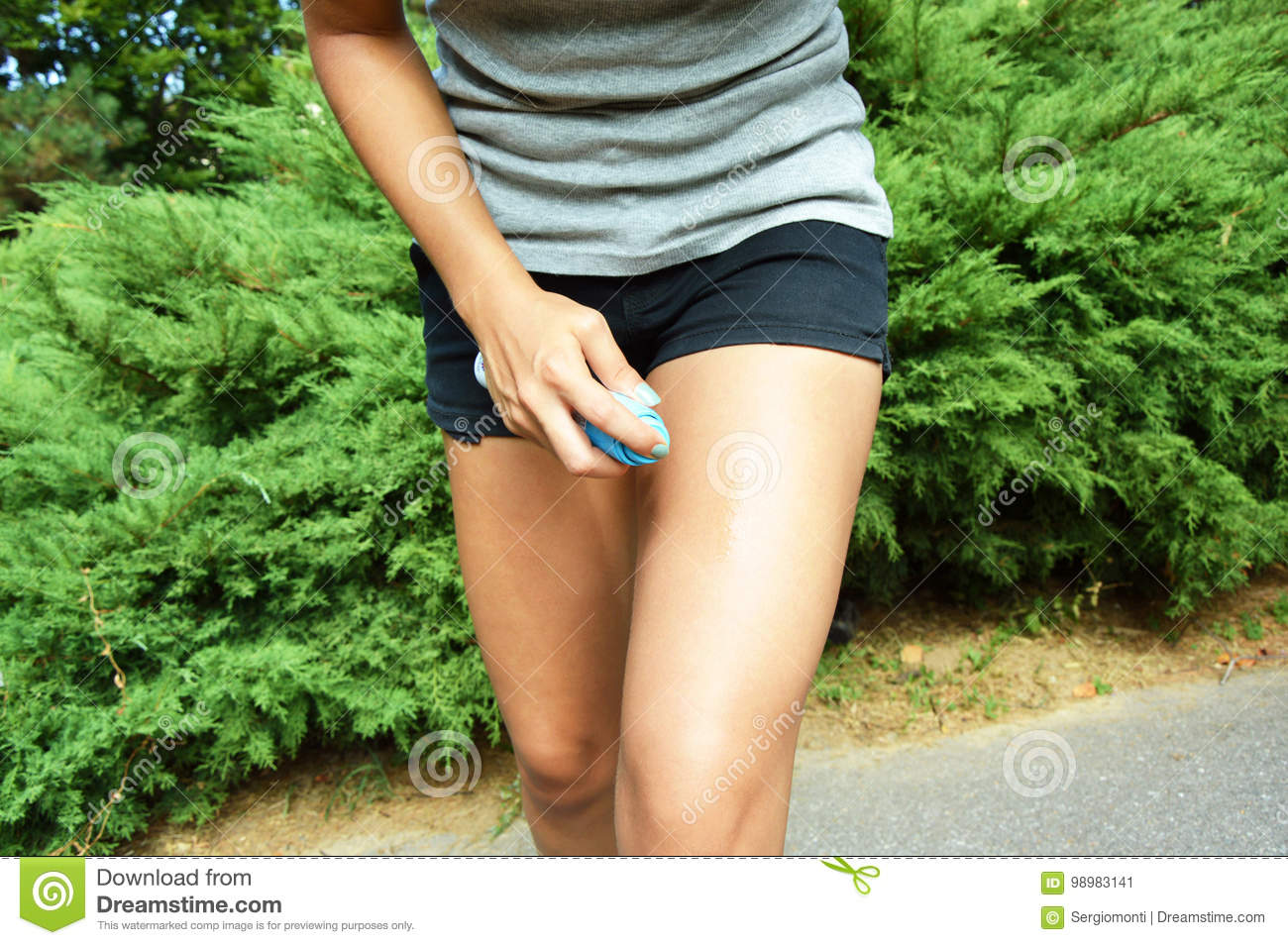 Mosquito repellent spray. Girl spraying insect repellent against bug bites on legs skin outdoor in nature forest using spray