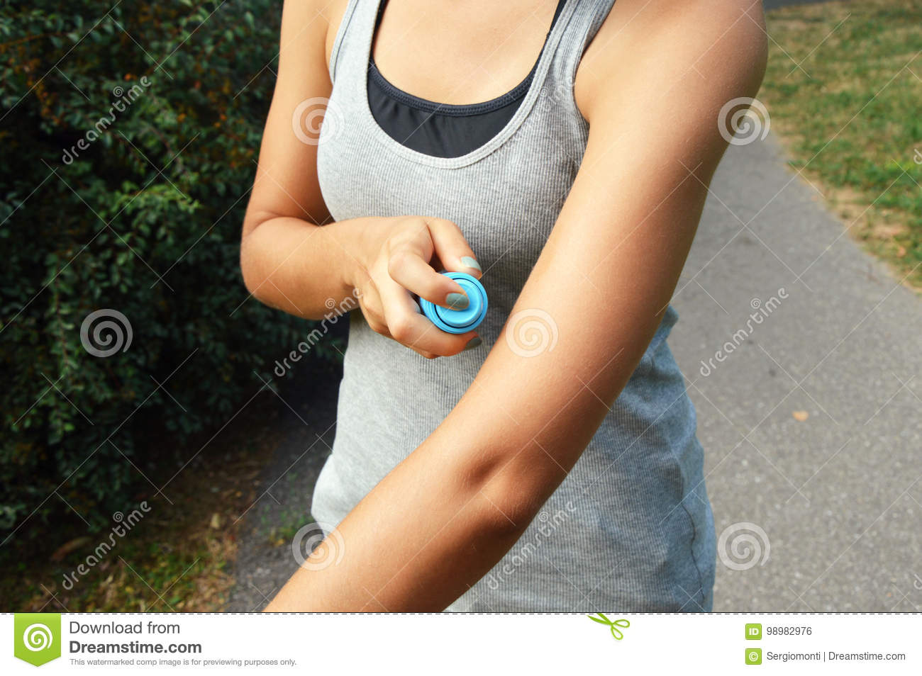 Mosquito repellent spray. Woman spraying insect repellent against bug bites on arm skin outdoor in nature forest using spray