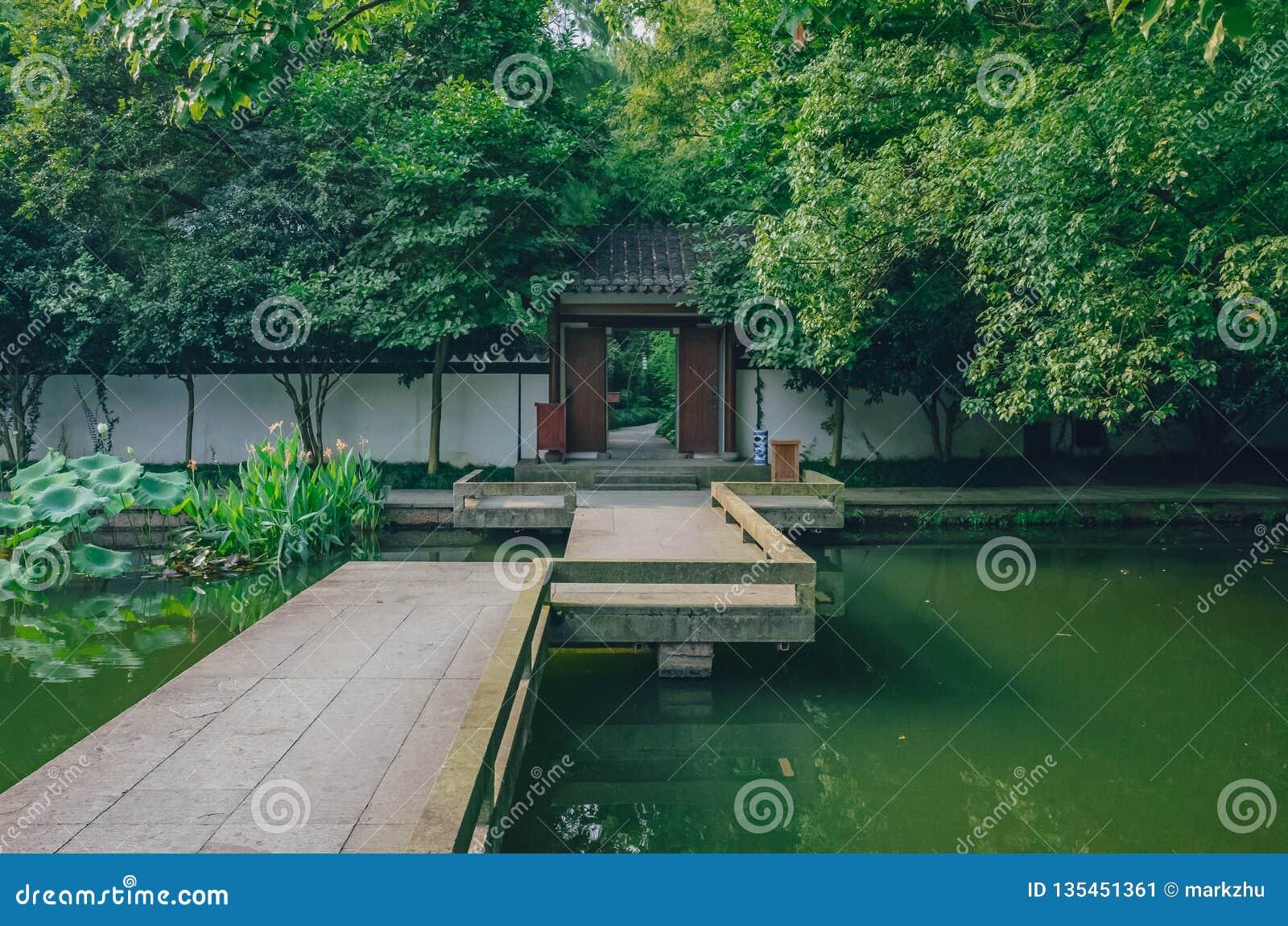 Most nad stawowy prowadzić drzwi pod drzewami, w chińczyka ogródzie, blisko Zachodniego jeziora, Hangzhou, Chiny