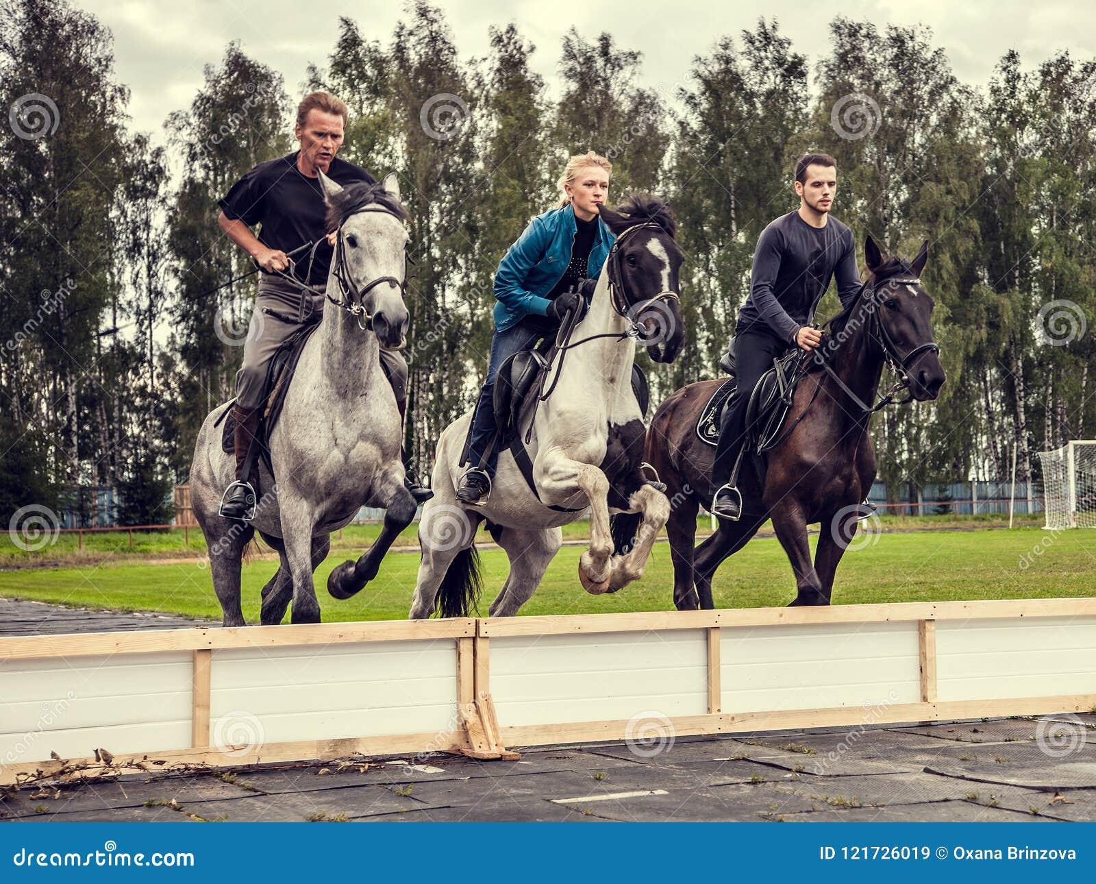 23 08 Mostra 2017 da região de Smolensk que salta no festival Três cavaleiros que saltam a cavalo synchronously sobre um obstácul