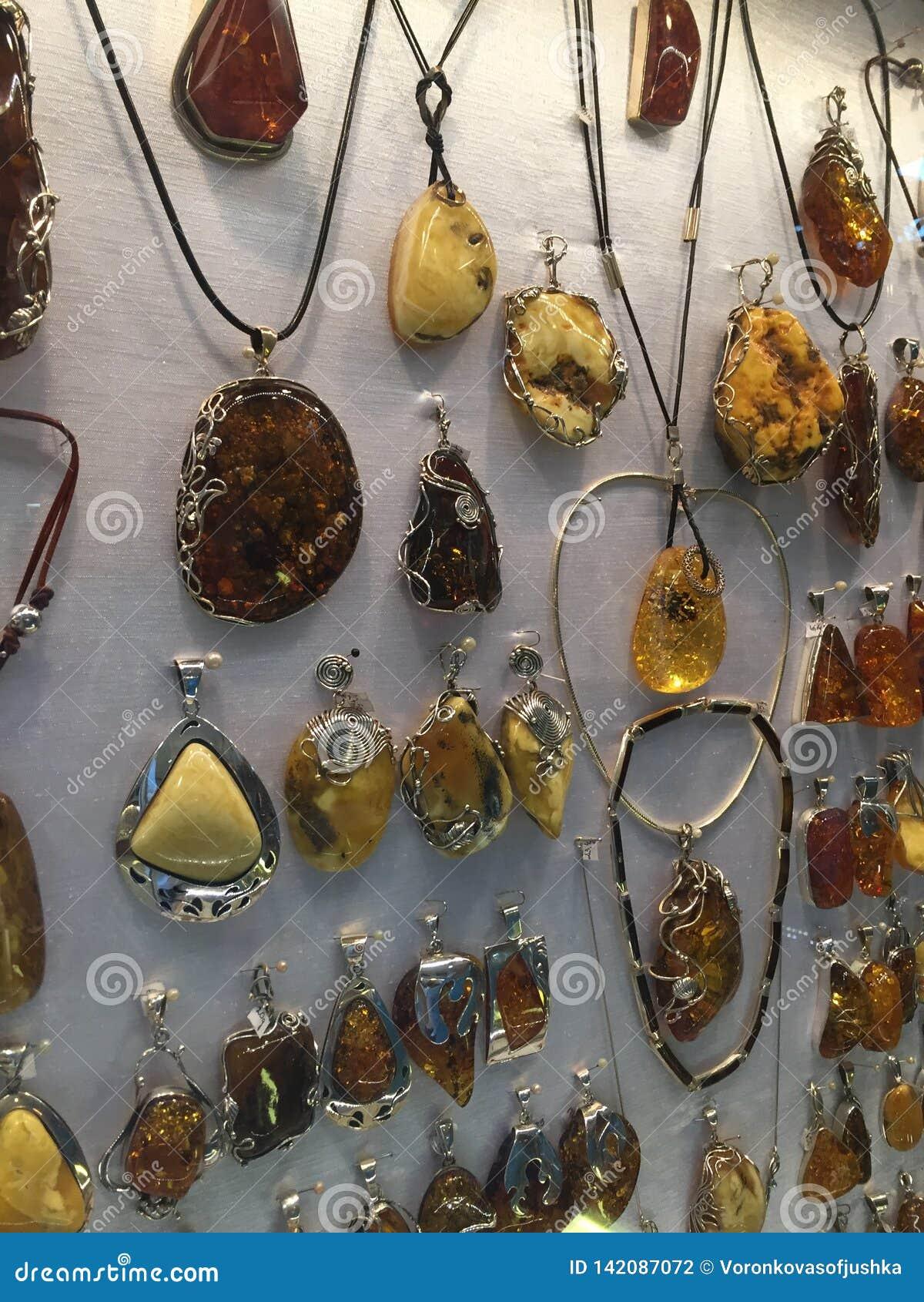 Mostra dos pendentes das mulheres bonitas feitos do âmbar