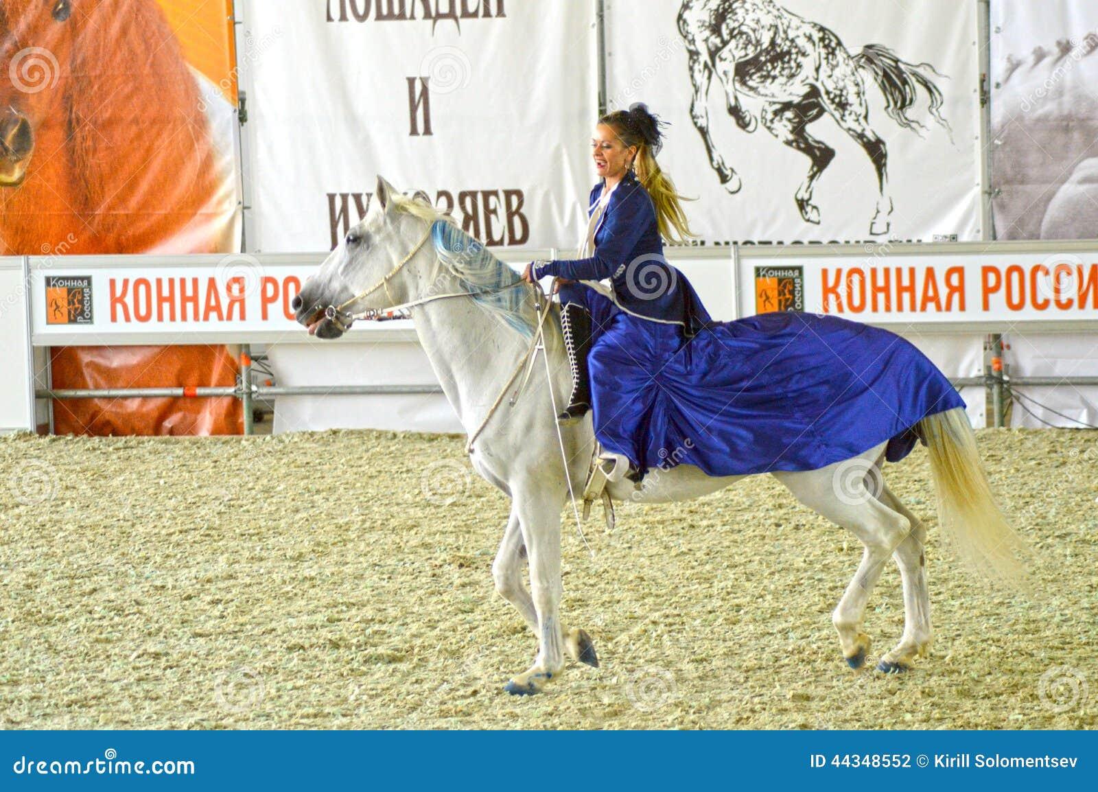 Mostra equestre internazionale durante la manifestazione Puleggia tenditrice della donna in un vestito blu scuro su un cavallo bi