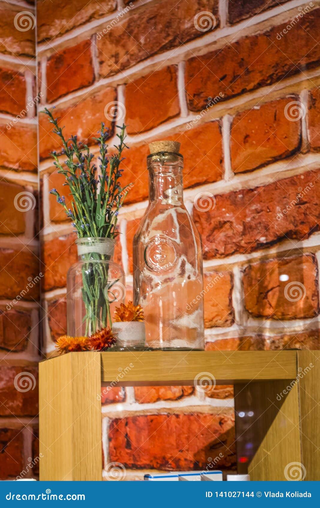 Mostra-janela na loja dos cosméticos no fundo do tijolos vermelhos Em garrafas de vidro do apoio de madeira e flores e ervas viol