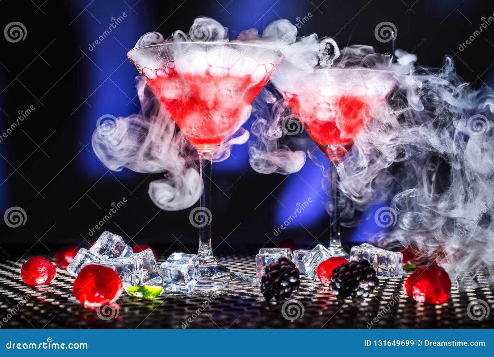 A mostra moderna da sobremesa da opinião de baixo ângulo ou o vidro do cocktail e do vapor vermelho do fumo ou do gelo seco, gelo