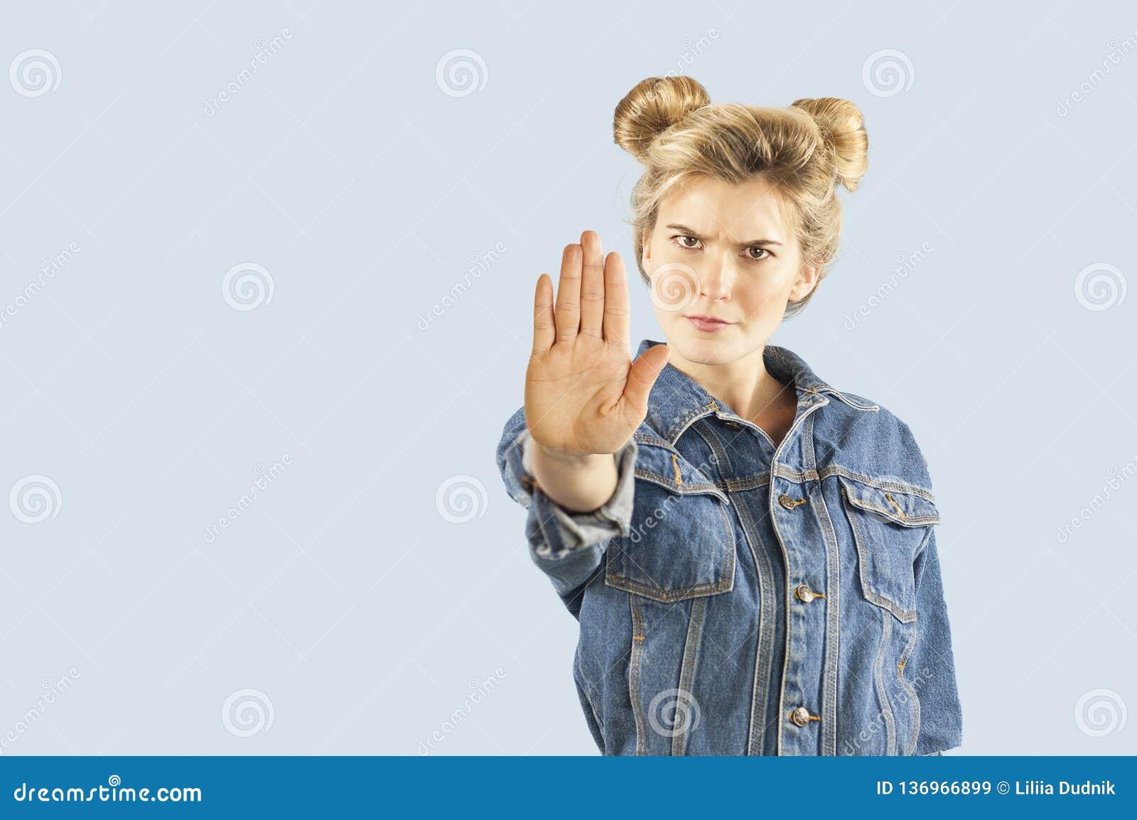 Mostras novas bonitas da menina do emrtional com mãos um sinal da parada em um fundo isolado Parada da palavra da menina