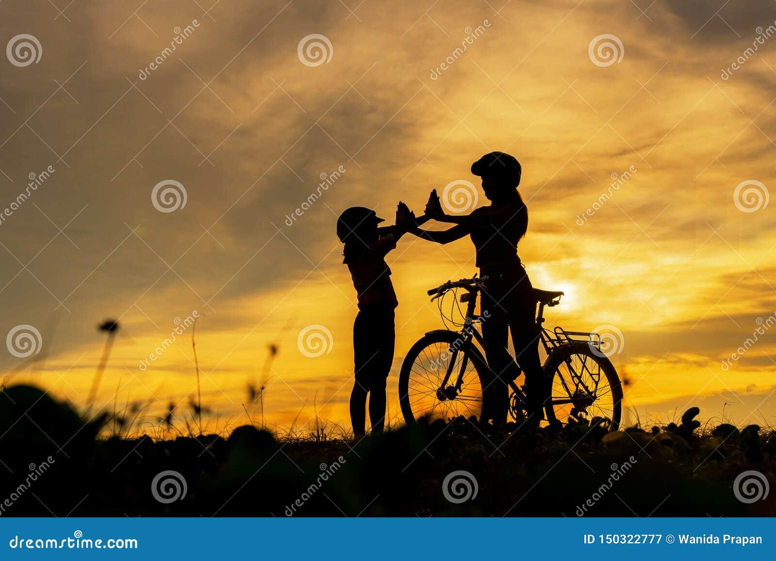 Mostre em silhueta a fam?lia bonita do motociclista no por do sol sobre o oceano Frio bicycling da mamã e da filha e para relaxar