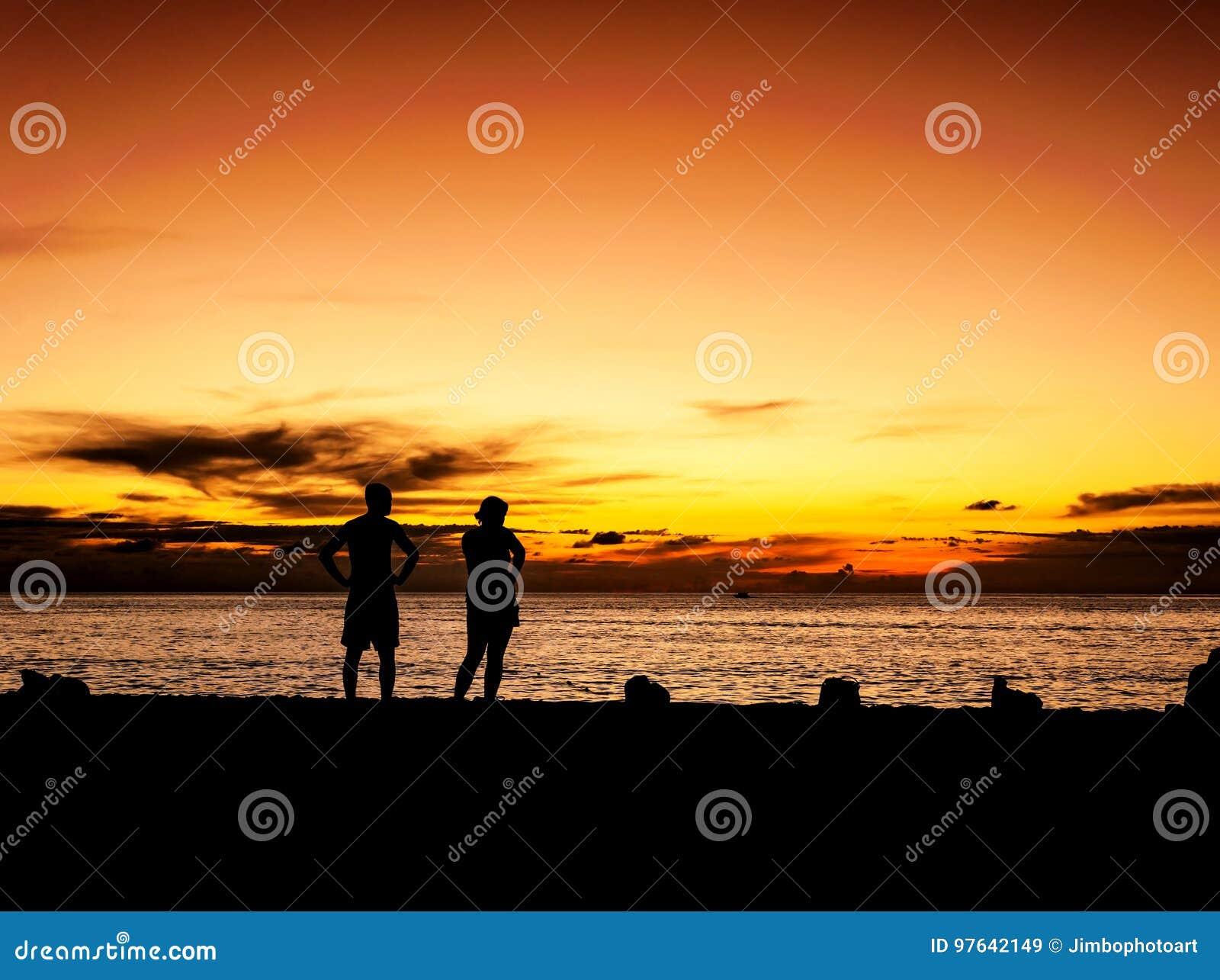 Mostre em silhueta o amante no por do sol da praia no crepúsculo