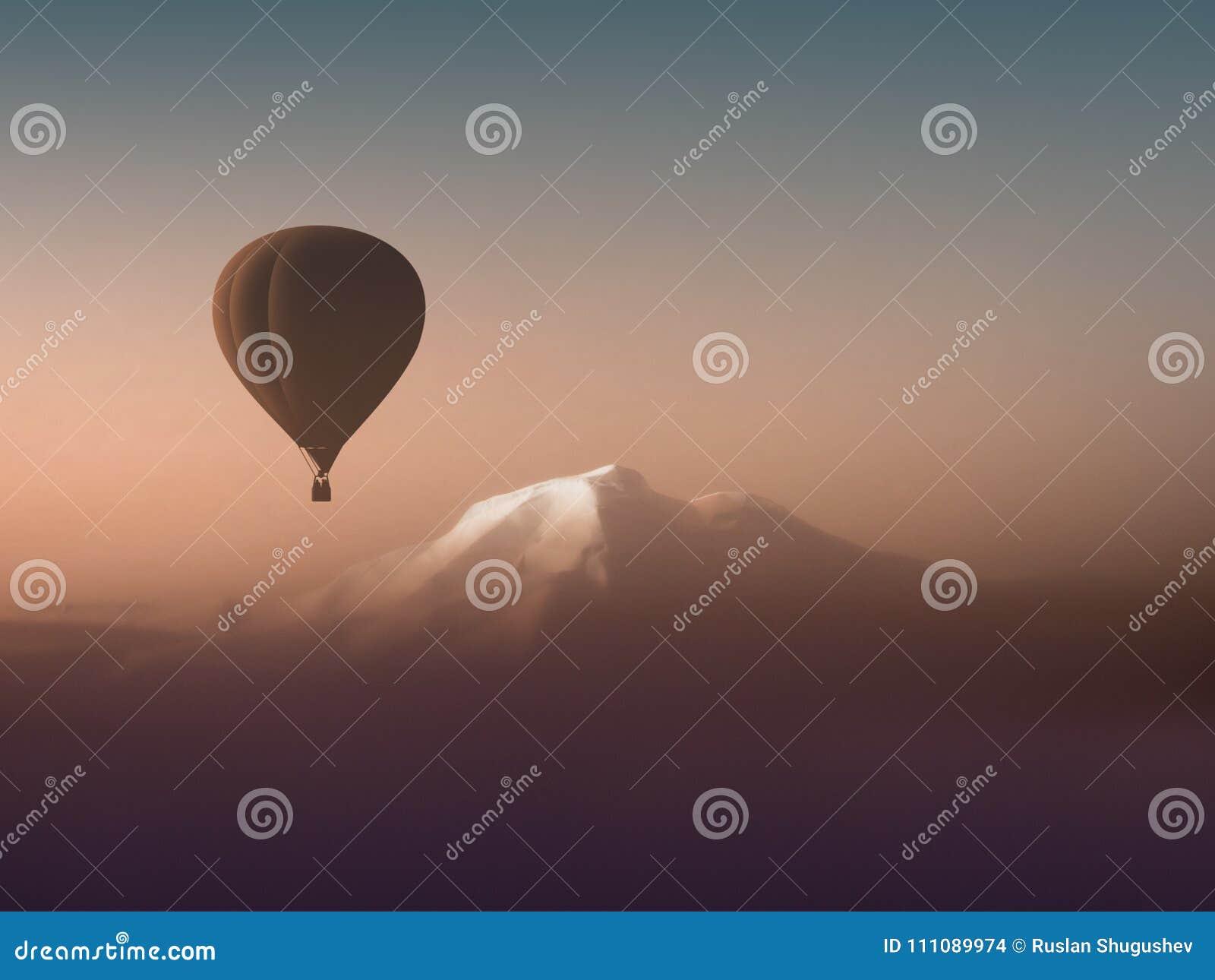 Mostre em silhueta o balão de ar quente que voa sobre as montanhas