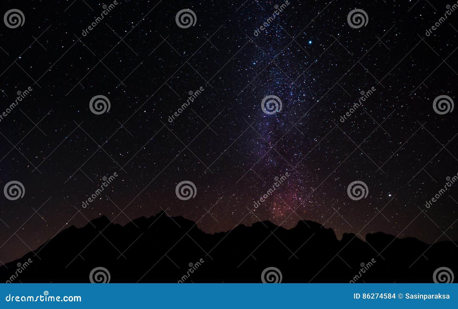 Mostre em silhueta o pico de montanha na noite com o céu completo das estrelas e da Via Látea
