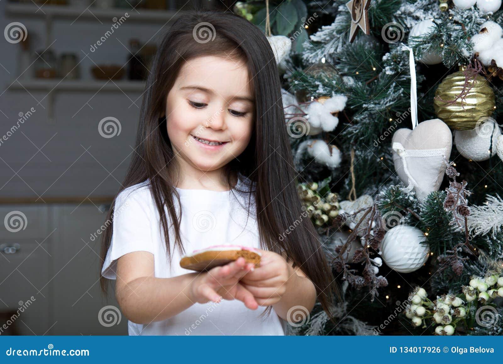 Mot julgranen en stående av lite flickan