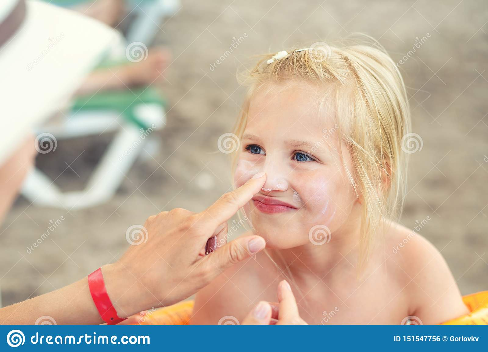 Mother applying sunscreen protection creme on cute little daughter face. Mom using sunblocking lotion to protect kid girl from sun