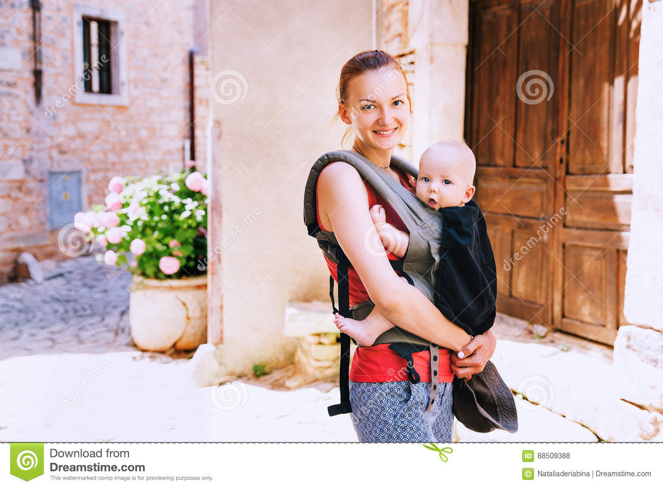 Mother With Baby In Carrier In The Old Town Of Pula, Croatia  Stock
