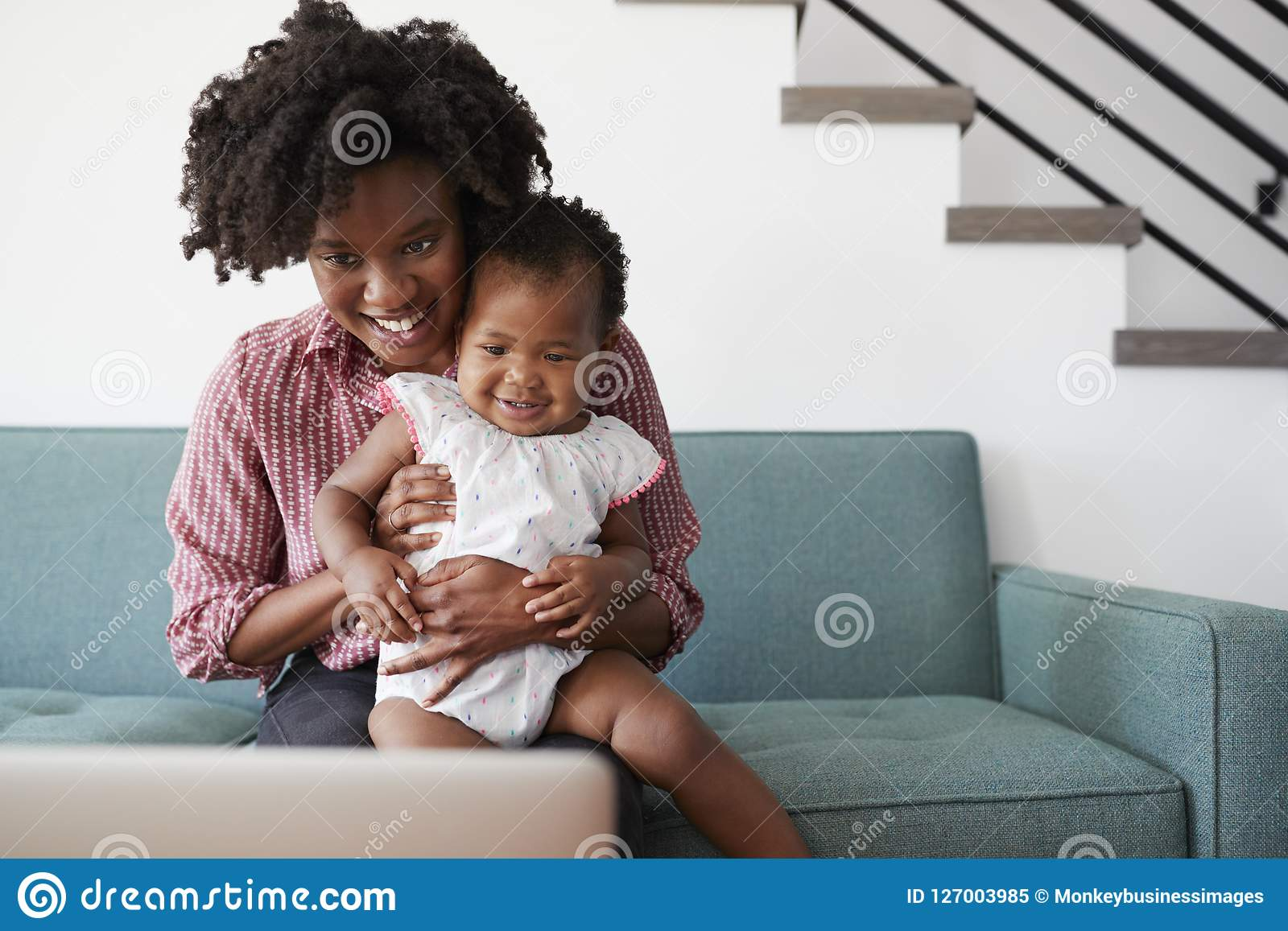 Mother With Baby Daughter Sitting On Sofa At Home Looking At Laptop Computer