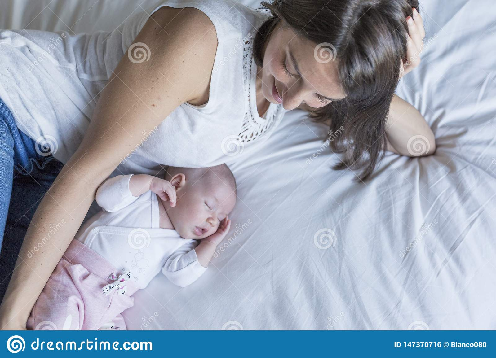 mother and baby at home lying on bed and relaxing. baby girl sleeping and mother looking at her. motherhood concept