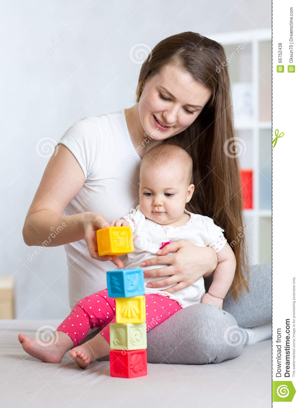 Mother and baby play with building blocks toy in nursery