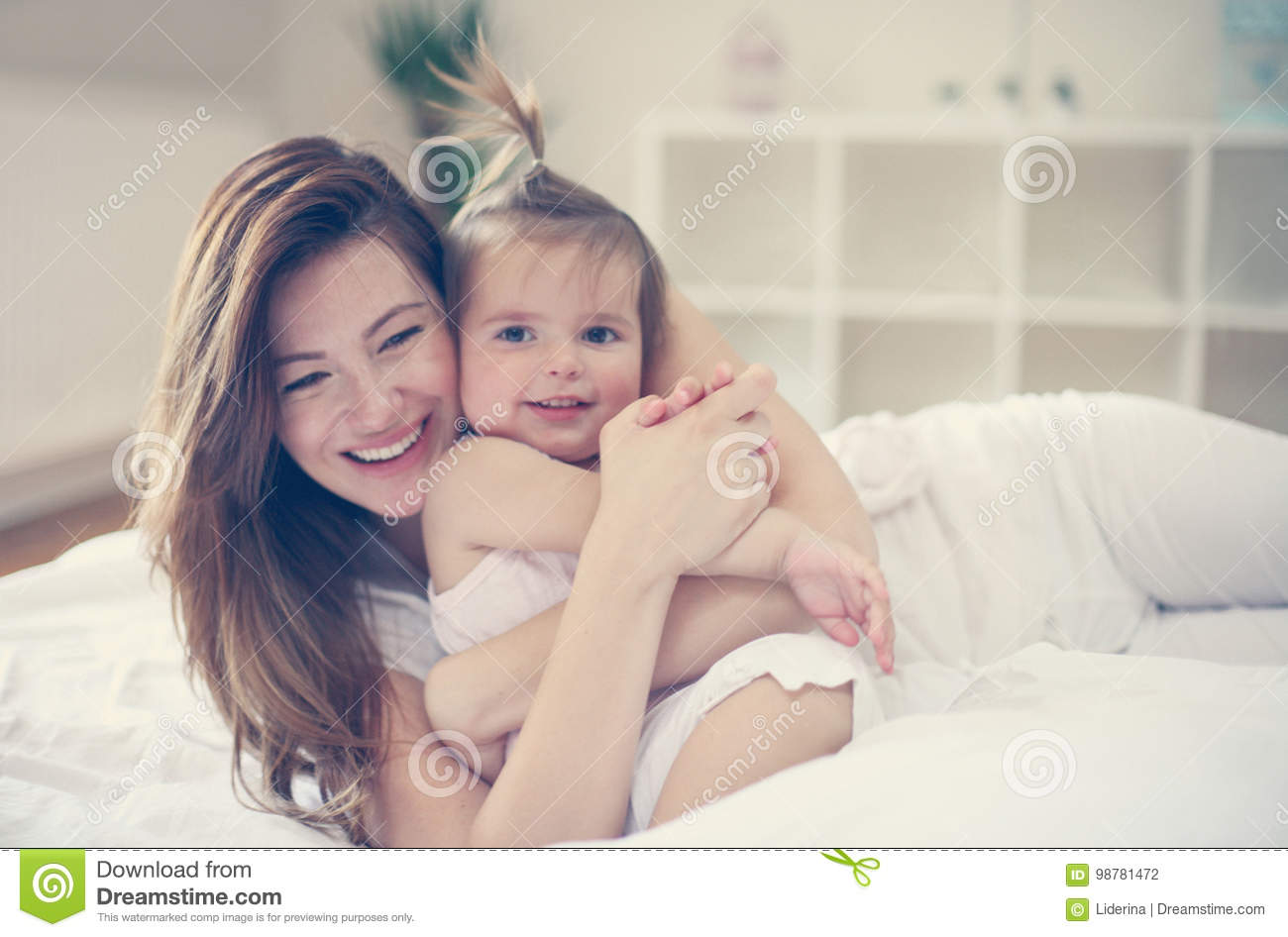 Young mother playing with her baby girl in bed mother enjoying in free time with her little cute baby mother hugging her little baby