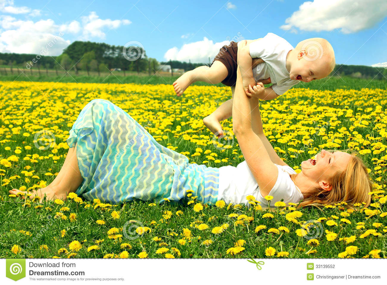 mother and baby playing in field stock photography image