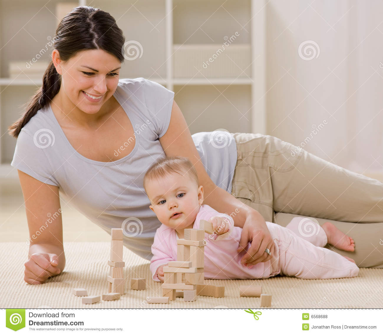 Mother and baby playing with wooden blocks