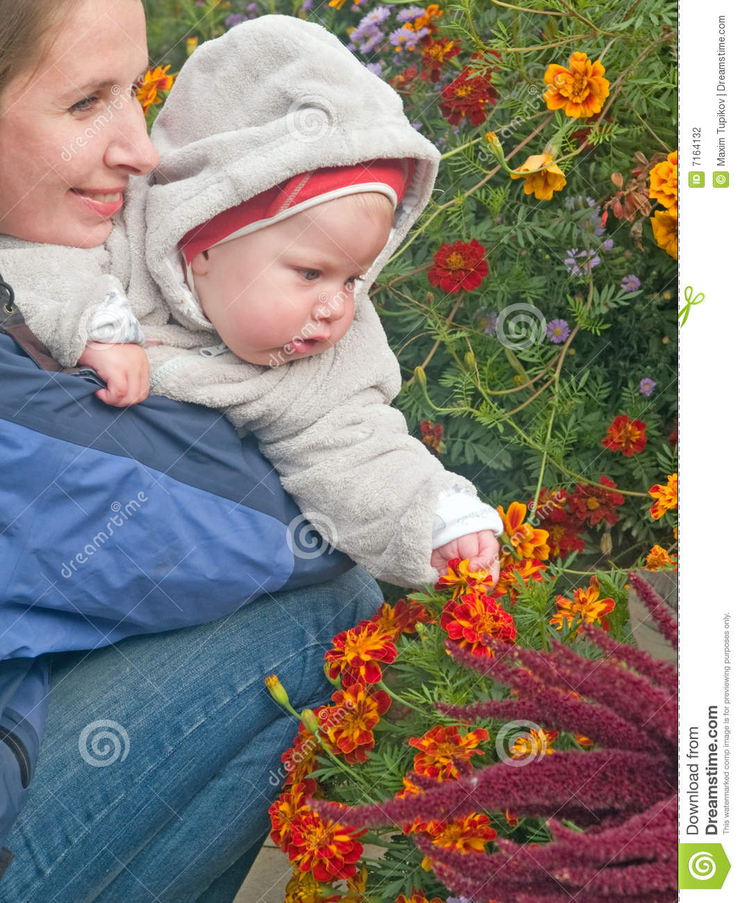 Mother with baby teaching flowers