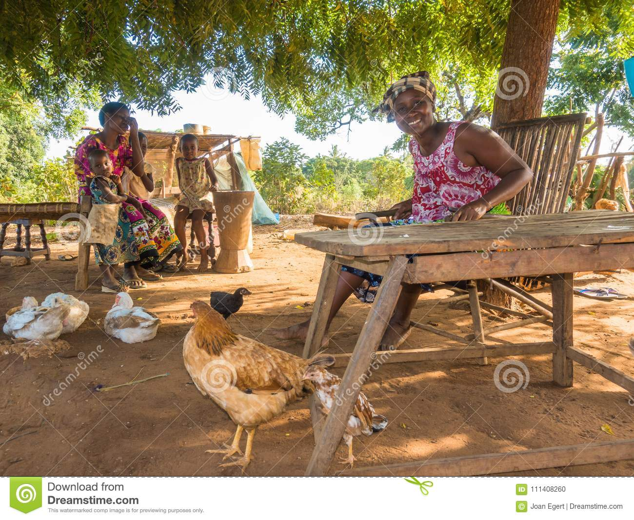 A Mother Belonging To The Kenyan Tribe Of The Giriama Sitting At A Table Of  Her Farmers Home With Her Two Small Baby Girls.