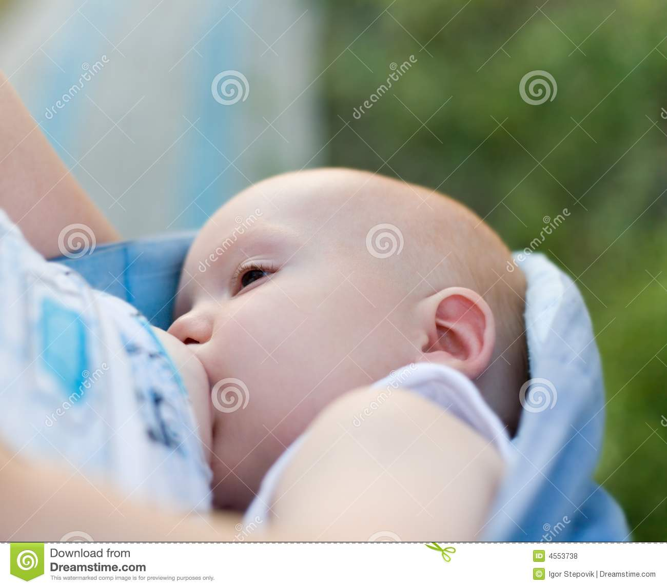 Mother breast feeding her infant in sling