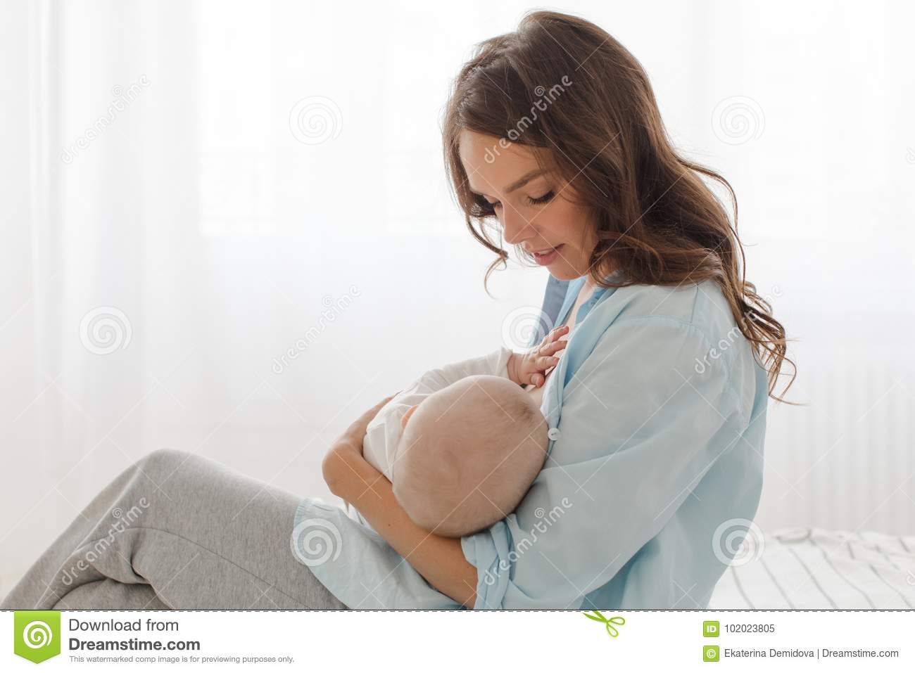 Mother breast feeding and hugging her baby boy