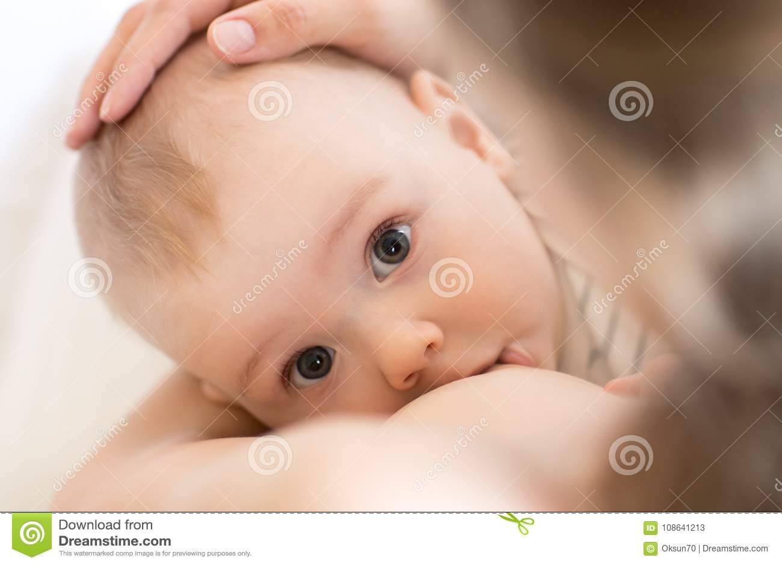 Mother breastfeeding her little boy. Mom nursing and feeding baby. Close-up portrait.