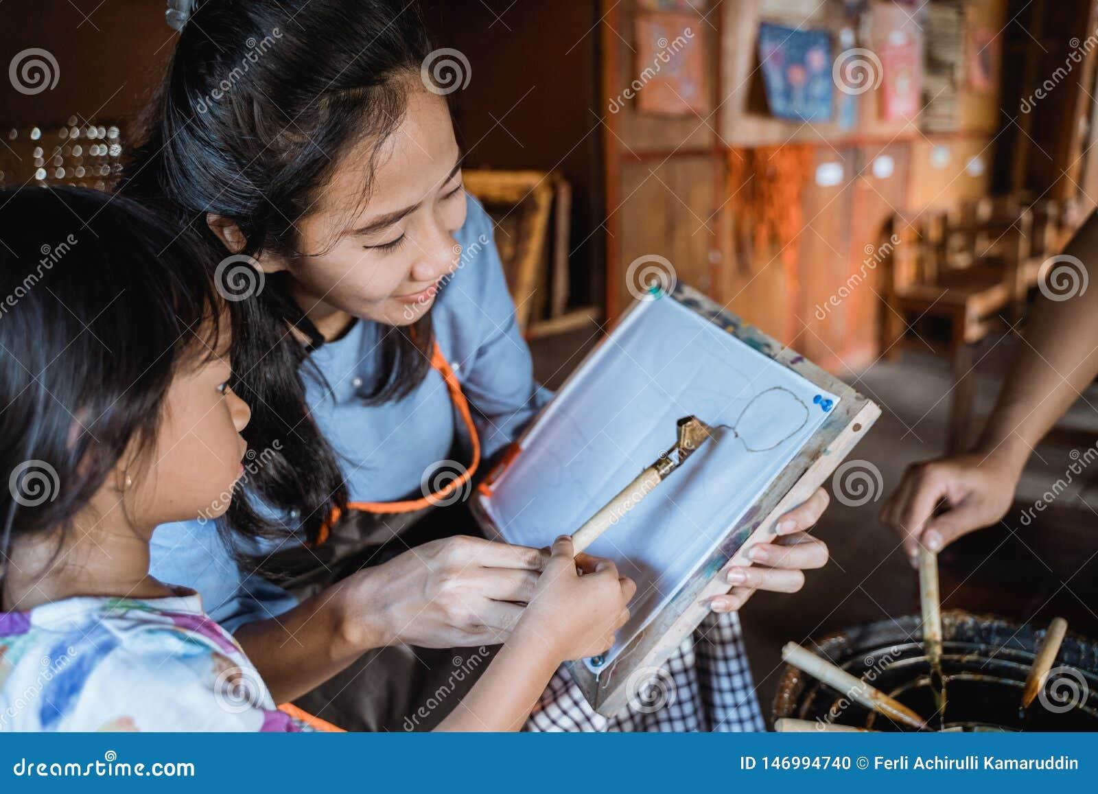 Mother and child asian making batik pattern