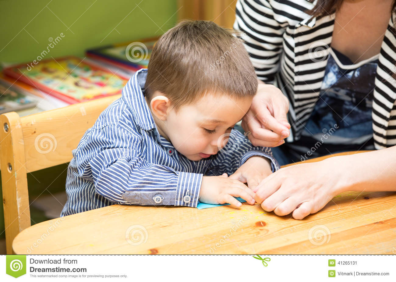 Mother and child boy drawing together with color pencils in preschool at table in kindergarten