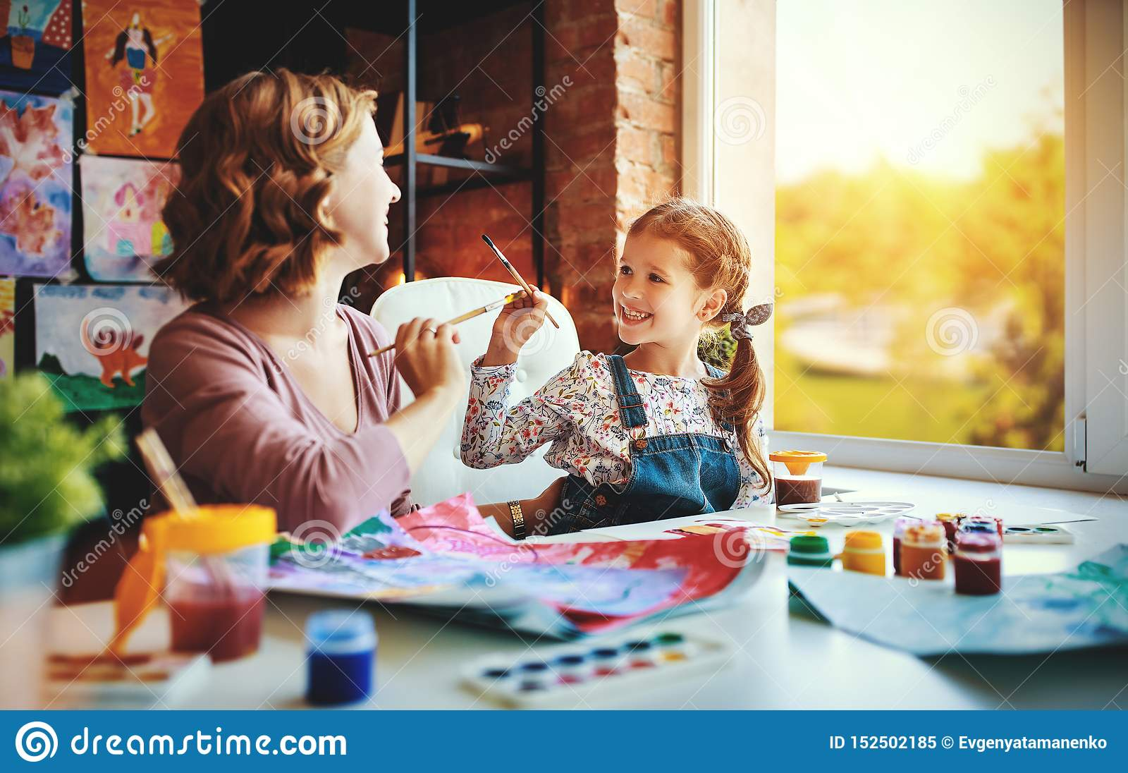 Mother and child daughter painting draws in creativity in kindergarten