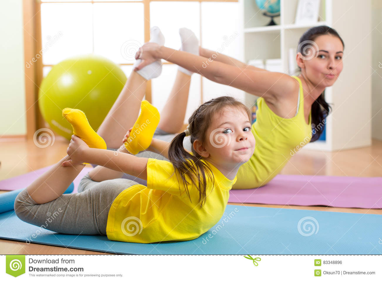 Mother and child doing fitness exercises on rug at home