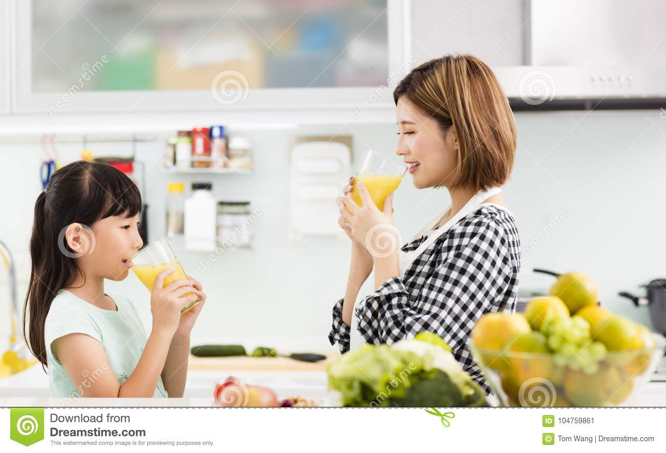 Mother and child in kitchen drinking juice